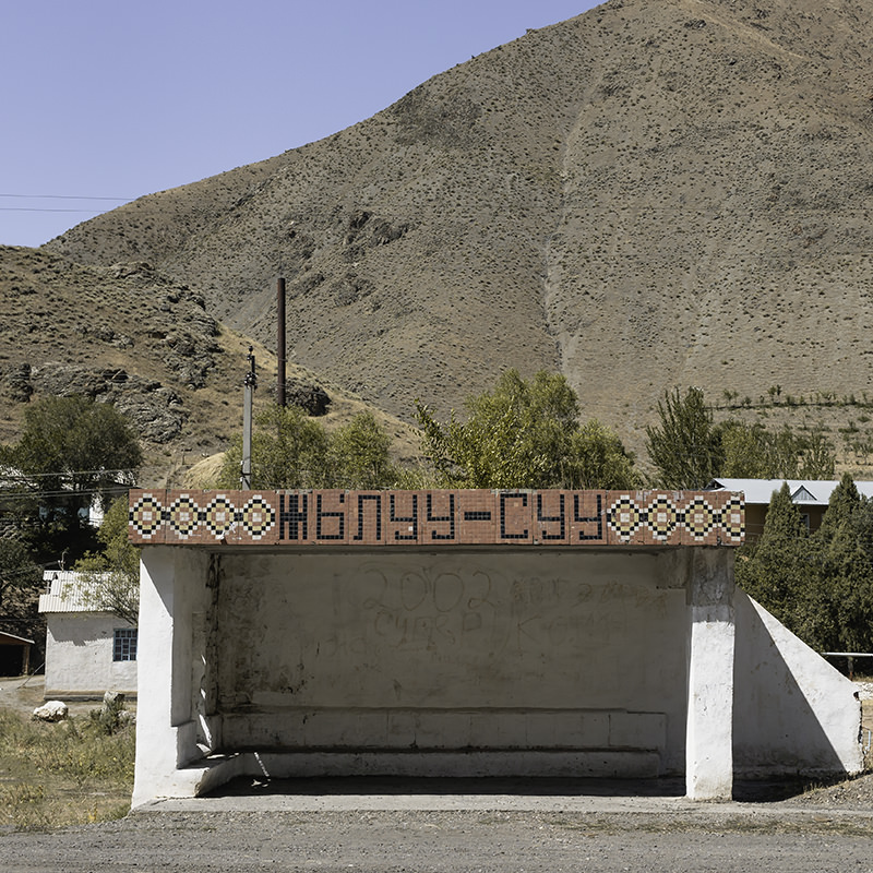 A Soviet bus stop in Kyrgyz village on Osh Road in the southwest, the village name inlaid with small tiles on top of a functional concrete block