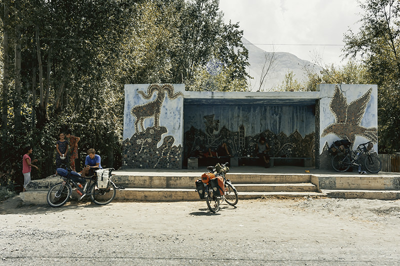 A Soviet bus stop on the Pamir Highway in Tajikistan. The bus stop is decorated with mosaics of Marco Polo sheep and an eagle. Three touring cyclists rest and three local girls wait in the shade of the trees