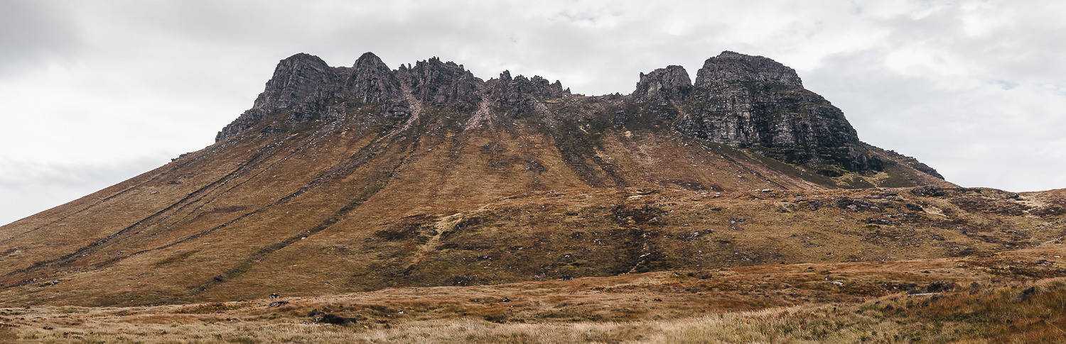 The jagged crown of hard rock that is the popular Scottish mountain Stac Pollaidh, accessible on a side trip from the North Coast 500 route