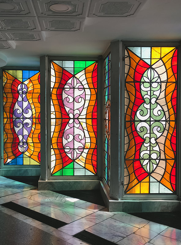 A colourful trio of stained glass windows with traditional Kyrgyz designs inside the Soviet era Bishkek Wedding Palace