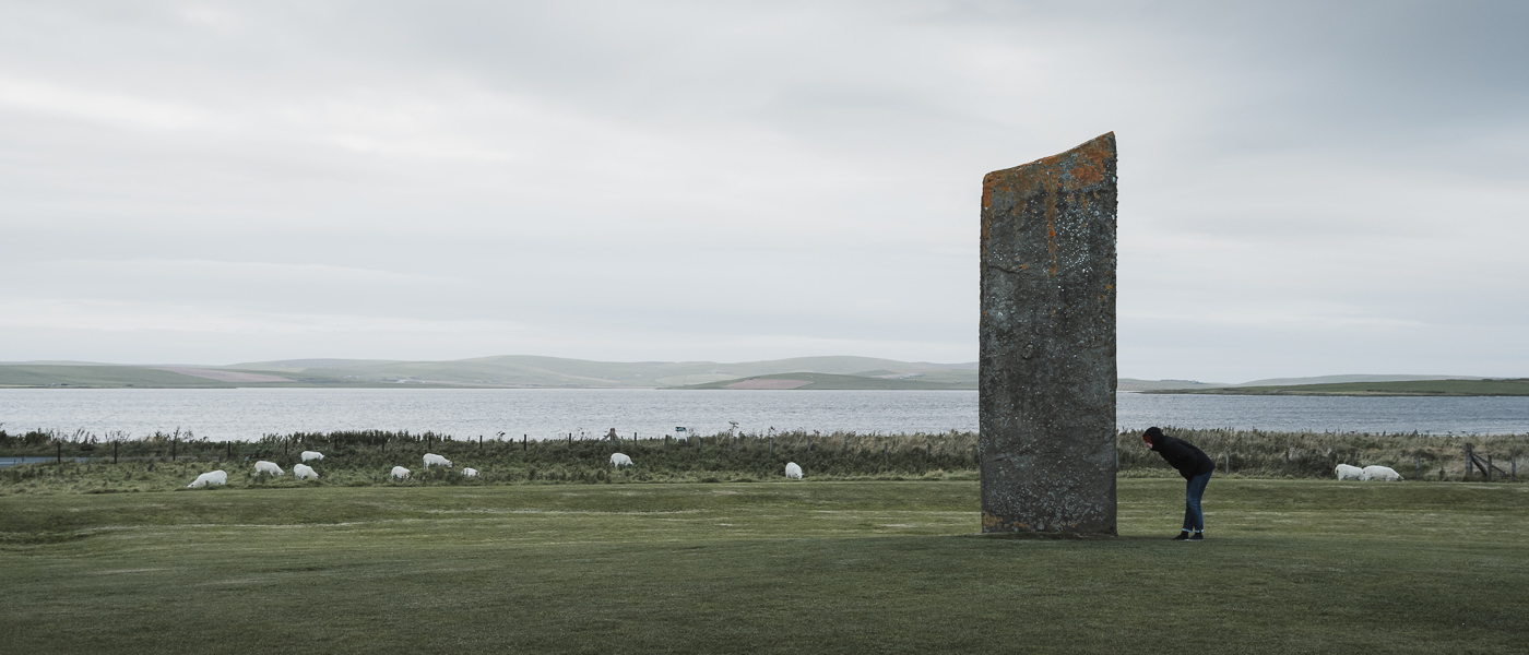A person inspects one of the four remaining Standing Stones of Stenness on Orkney Mainland in Scotland
