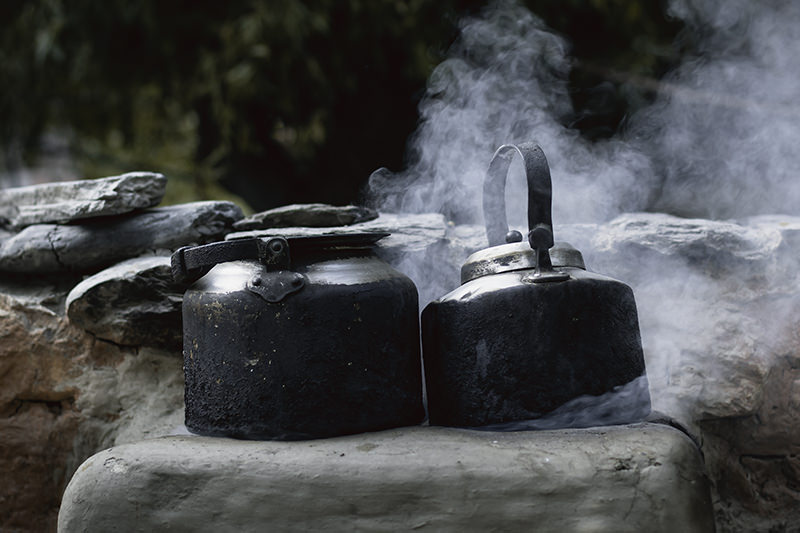 Two blackened kettles steaming on a mudbrick stove in the streets of Kagbeni