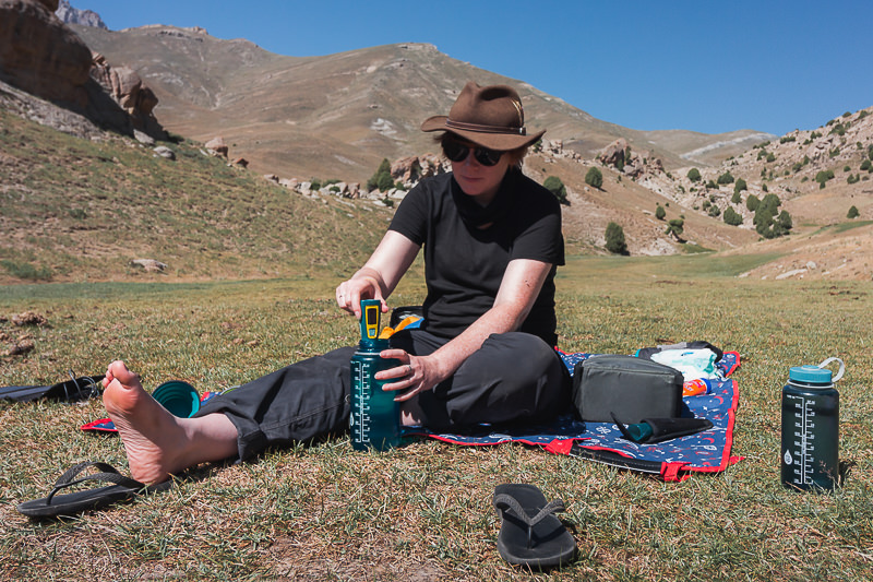Treating water in a Nalgene bottle with a Steripen, a vital part of backpacking camping gear