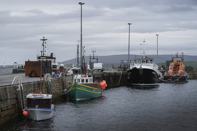 Boats line the quayside under grey skies at Stromness Harbour in the Orkney Islands