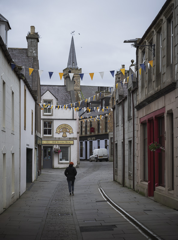 A lone person walks down a deserted flagstoned street at dusk in Stromness on Orkney Mainland