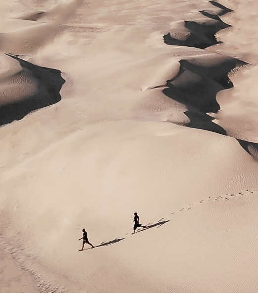 Two tiny figures wander down the sand in the vast expanse of Oman's Sugar Dunes