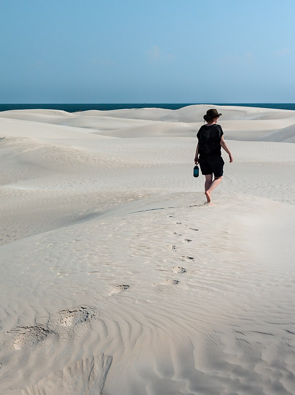 A person walks alone through the white Sugar Dunes in Oman