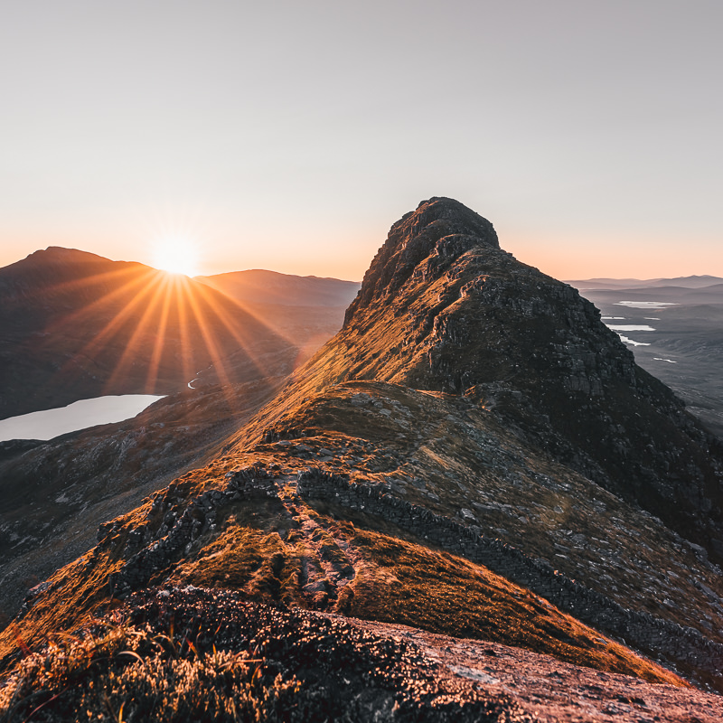 A sunburst rises over the distant mountain and bathes Suilven's eastern summit with its golden glow
