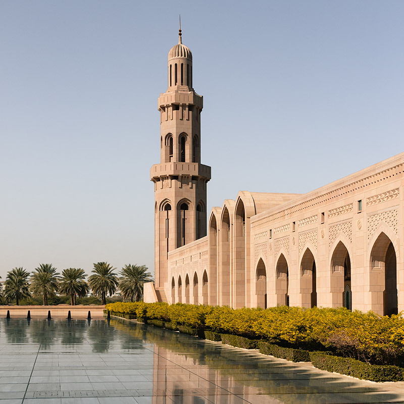 The Sultan Qaboos Grand Mosque in Muscat, Oman, glowing in the sun and reflected in the mirrorlike surface of the courtyard flagstones.