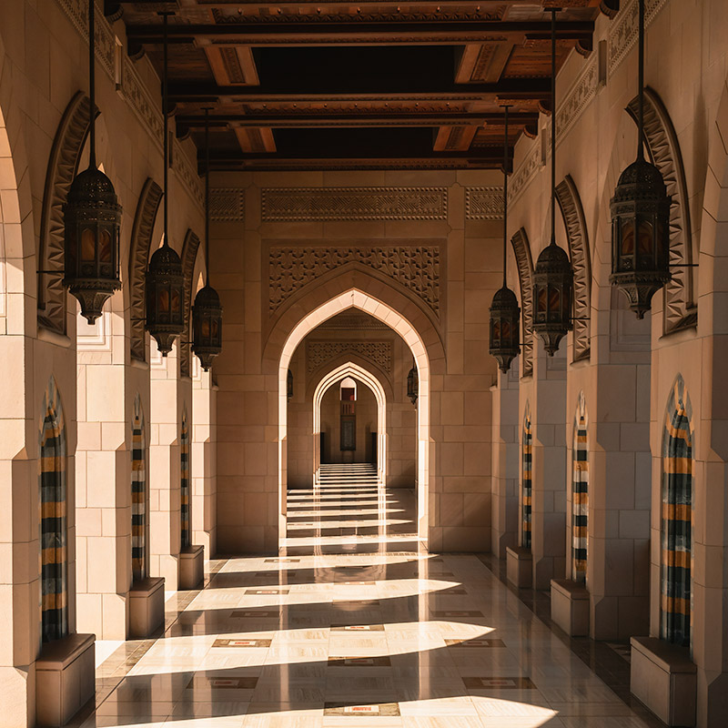 The outlying corridors in the grounds of the Sultan Qaboos Grand Mosque in Oman. The light and shadow cast by the arches makes an interesting geometric pattern