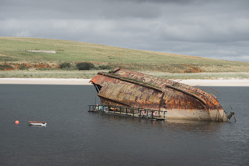 The remains of the Reginald rise above the water line in East Weddell Sound, next to Churchill Barrier 3 in the Orkney Islands