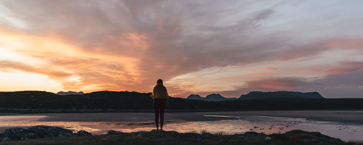 A person stands on the shore watching a dramatic sunrise at low tide on Achnahaird Beach in Scotland
