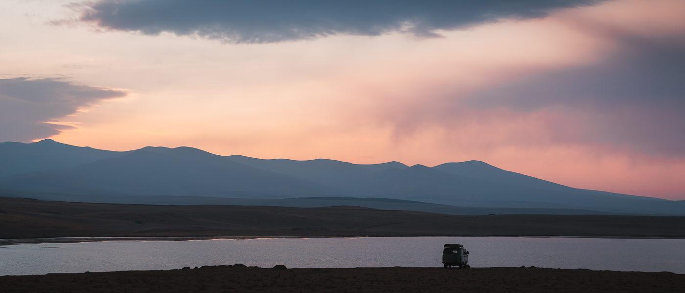 Red and orange sunrise hues light the sky beneath dark clouds at Madatapa Lake in Javakheti, Georgia