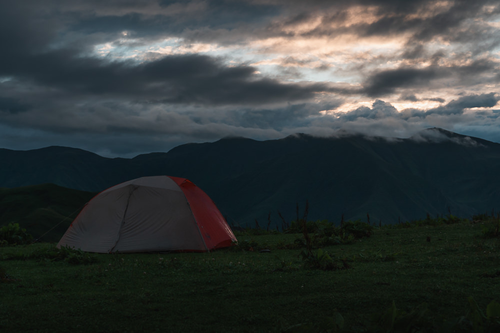 The sunrise breaks through dark clouds above the mountains, casting a little light on the tent in the foreground at the Mountain Spring camp on Day 5 of the Tusheti Pankisi Valley trek