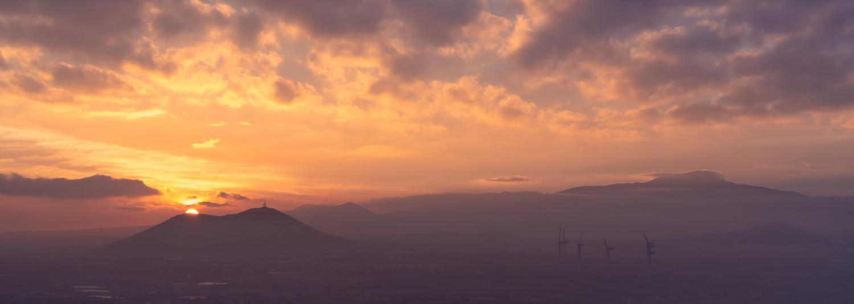 An orange sunrise under a purple cloudy sky on Jeju Island