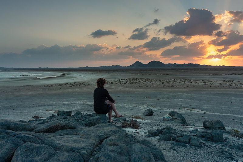 Sunrise from our campsite on Masirah Island. Kim sits on the rocks and watches the orange glow rise behind the distant mountains.