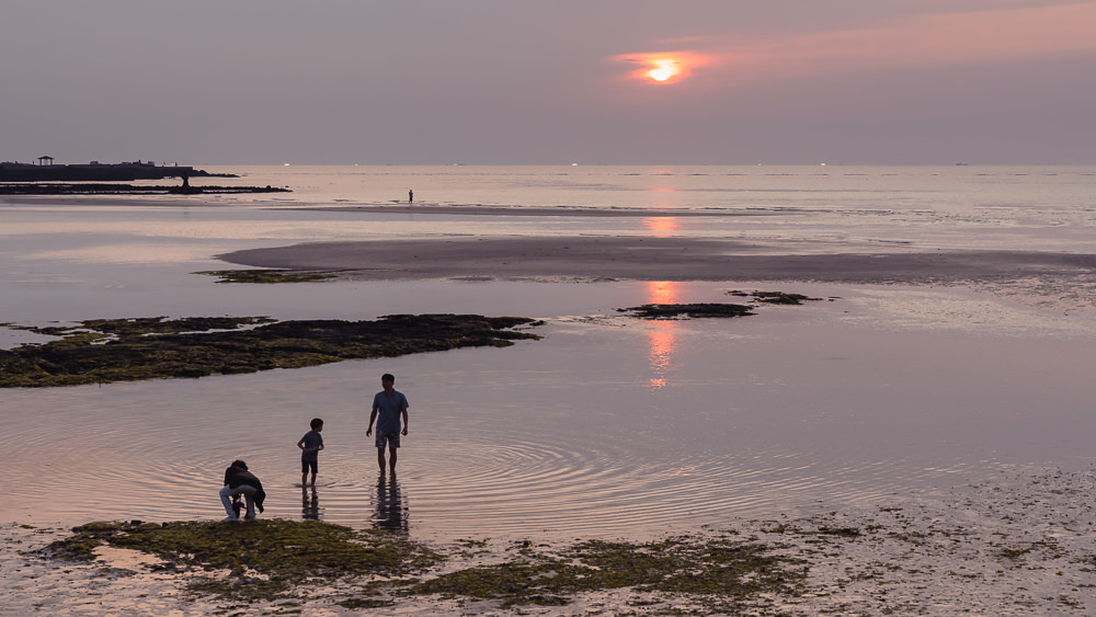 A family playing at sunset in the shallow water at Geumneung Beach on Jeju