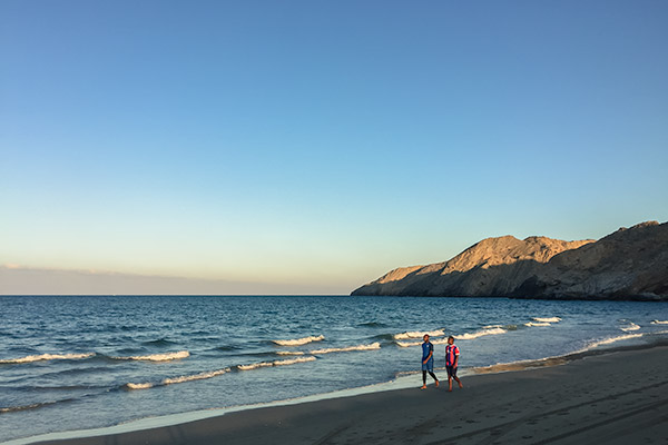 Two men walk the shoreline at Yiti Beach in Oman as the sandy coloured mountains behind glow in the setting sun
