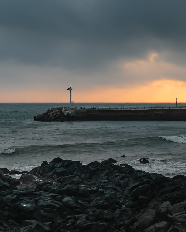 Sunset colours showing on the horizon beneath dark clouds as waves crash in past the breaker at Yongsu Port