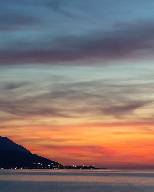 Sunset hues above the twinkling lights of Bukha, seen from Al Jadi Beach in Musandam