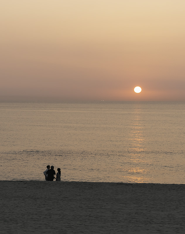Three people stand together on Gwakji Beach as the sun nears the horizon out at sea
