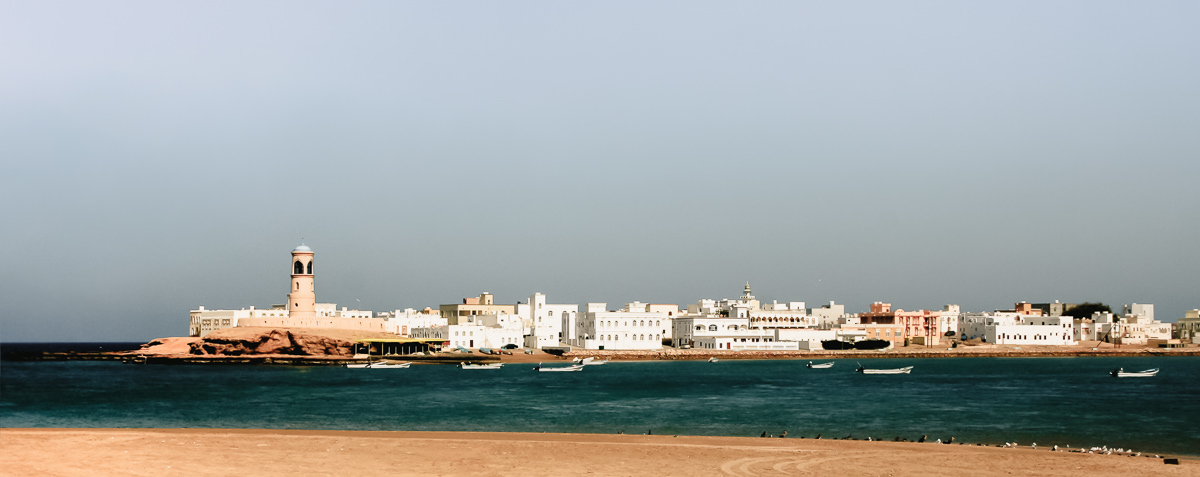 the view from Sur across the inlet to the sandy coloured lighthouse and white buildings at Al Ayjah