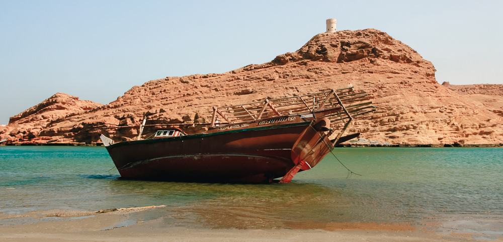 A dhow in the water at the shipyard, with one of the Al Ayjah watchtowers behind, one of the things to see on our 10 day Oman itinerary