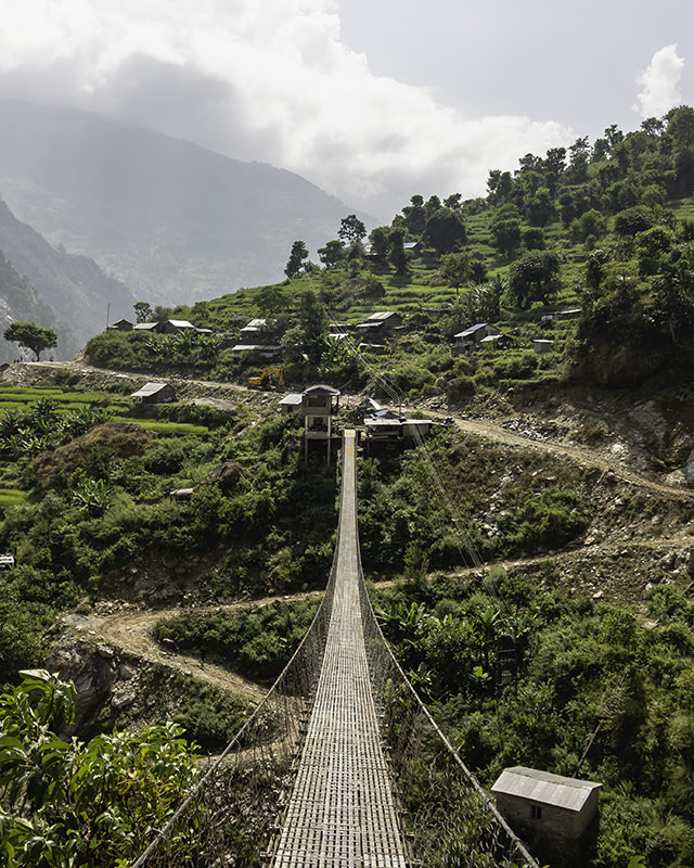 A suspension bridge spans the valley above rice fields and a snaking dirt road on day two of the Manaslu Circuit Trek