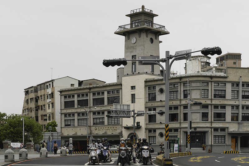 The distinctive 1930s Tainan City Fire Museum (M) with a group of motorbikers stopped at the traffic lights
