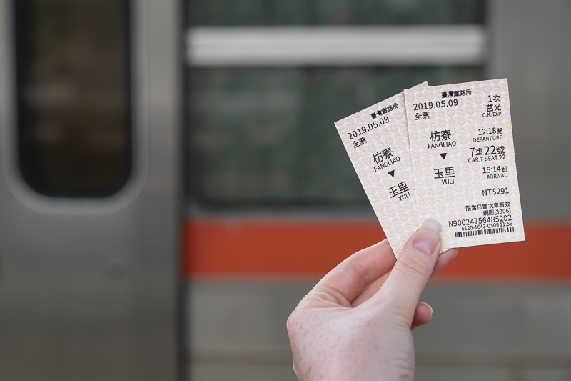 A person's hand holding a pair of Taiwanese train tickets in front of a blurred background train