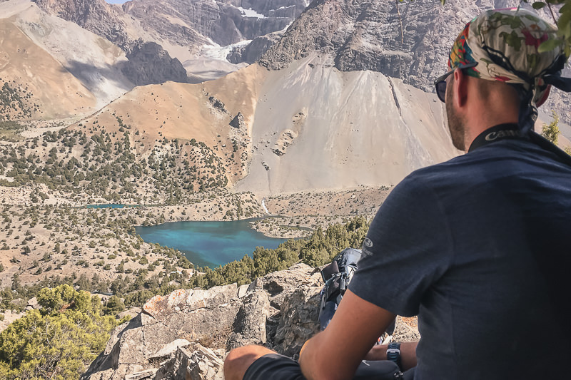 A trekker resting in the shade with a view down to Alauddin Lake in Tajikistan's Fann Mountains