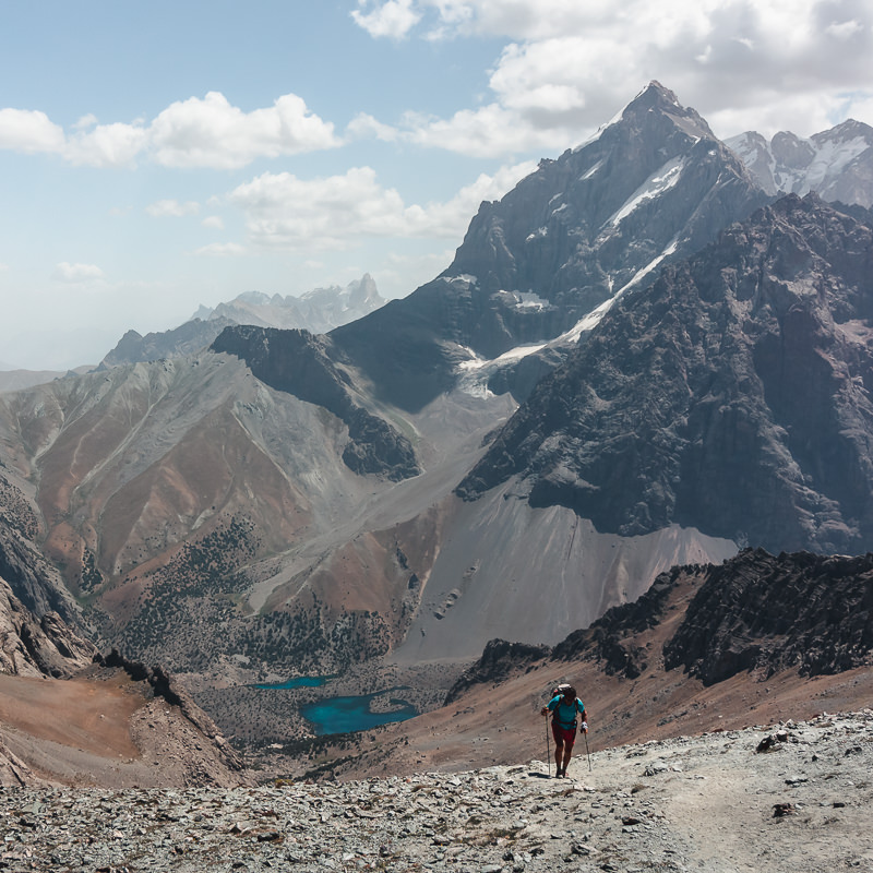A hiker reaches Alauddin Pass in the Fann Mountains