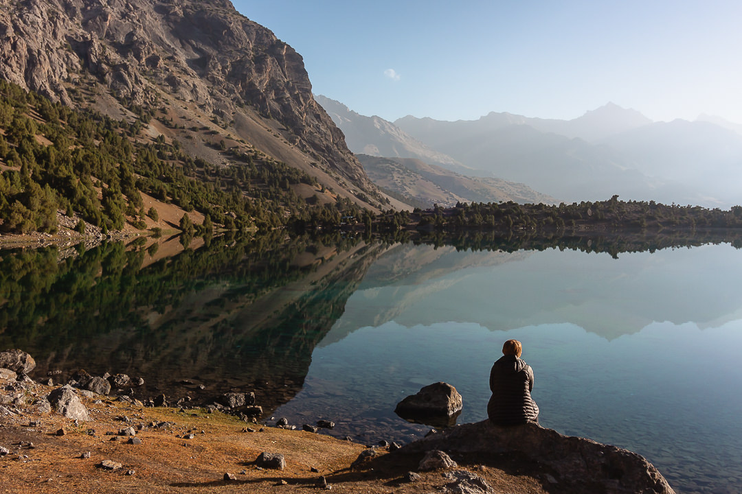 A hiker sits on a rock watching the still reflection on Alauddin Lake in Tajikistan's Fann Mountains