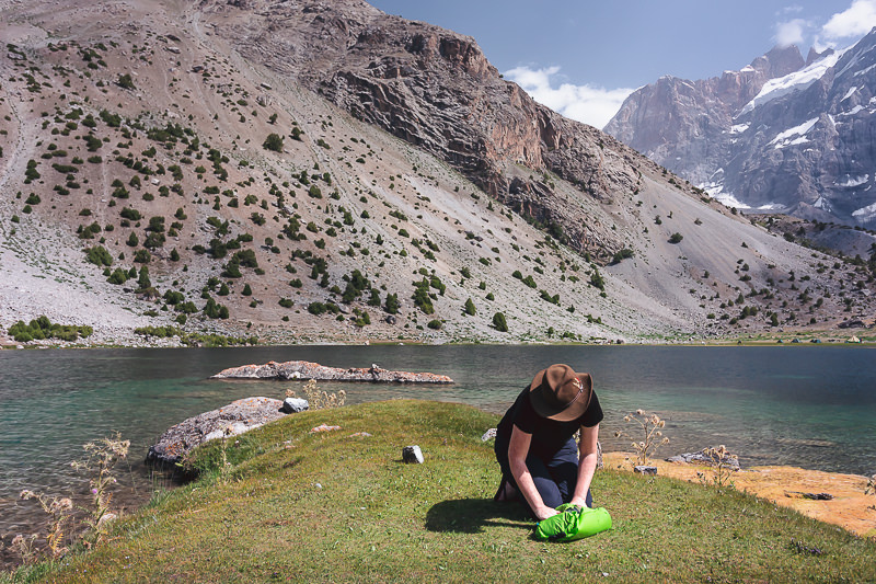 A person kneels on a lakeshore in the Fann Mountains washig clothes in the Scrubba