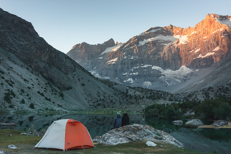 Two trekkers sit on a rock beside their tent watching the first of the day's sun hitting off the mountains opposite