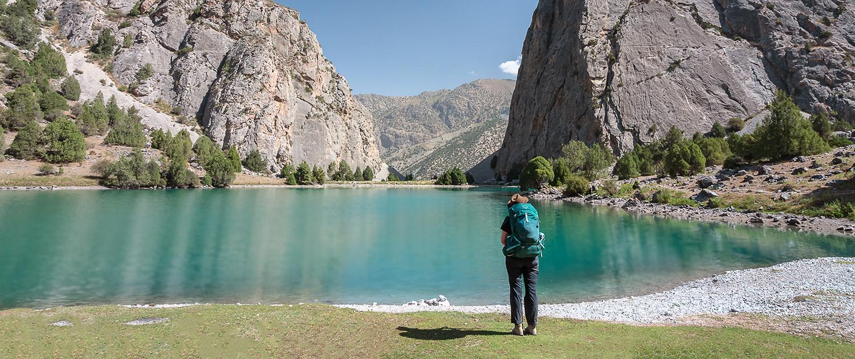 A hiker stands and admires the aquamarine Chukurak Lake in Tajikistan's Fann Mountains