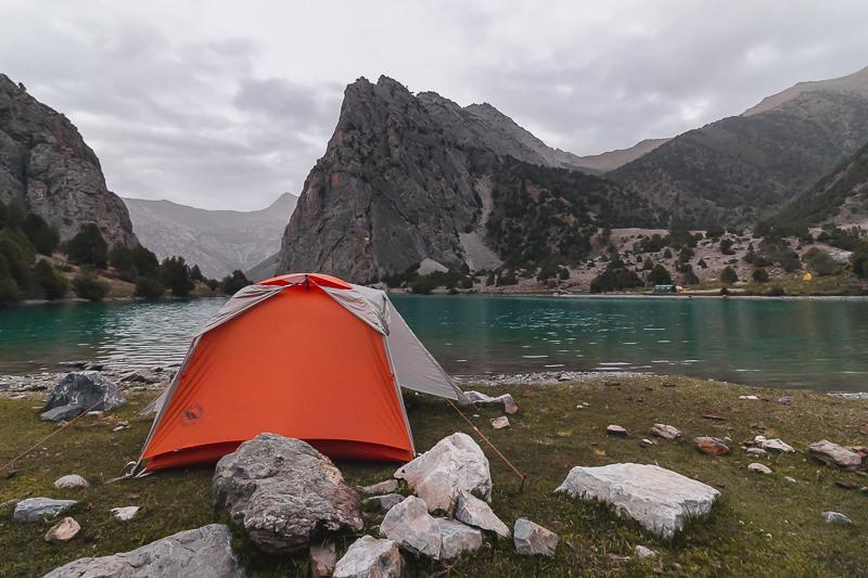 An orange tent pitched at the shore of Chukurak Lake in Tajikistan's Fann Mountains