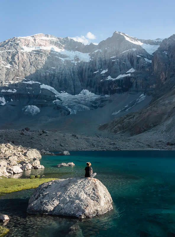 Admiring the mountain view, a person sits on a large rock in Dushakha Lake in Tajikistan's Fann Mountains