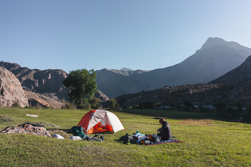 A hiker sitting on a mat next to her orange tent in a meadow near the 7th lake of the Haft Kul in Tajikistan's Fann Mountains
