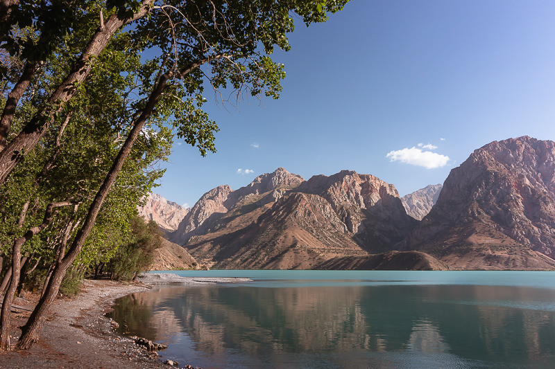 Trees line the shore of turquoise Iskanderkul, with mountains on the opposite shore