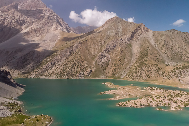 An aerial view of green coloured Kulikalon Lake and the surrounding mountains in Tajikistan
