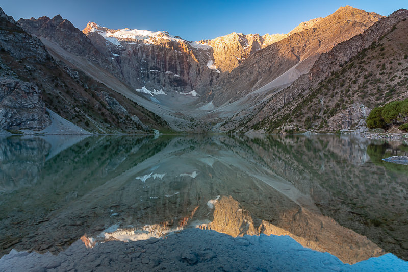 Sunrise at Kulikalon Lake in the Fann Mountains of Tajikistan. Fed by glacial meltwater, this is the biggest of three lakes in an amphitheatre-like valley, surrounded on all sides by mountains