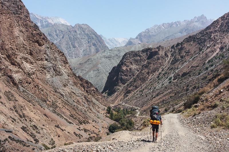A trekker following the trail down towards the Archamaidan Valley in the Fann Mountains of Tajikistan