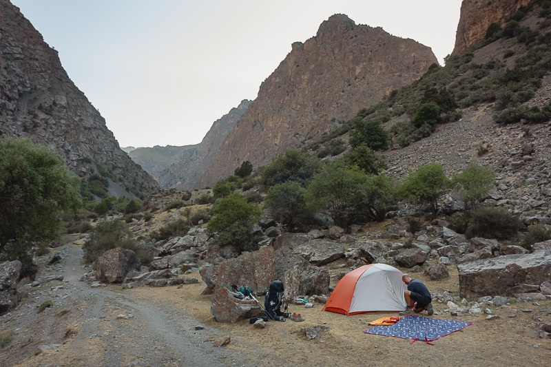 A hiker pitching a tent in a clearing among the mountains in the narrow Sarymat River Valley in Tajikistan's Fann Mountains