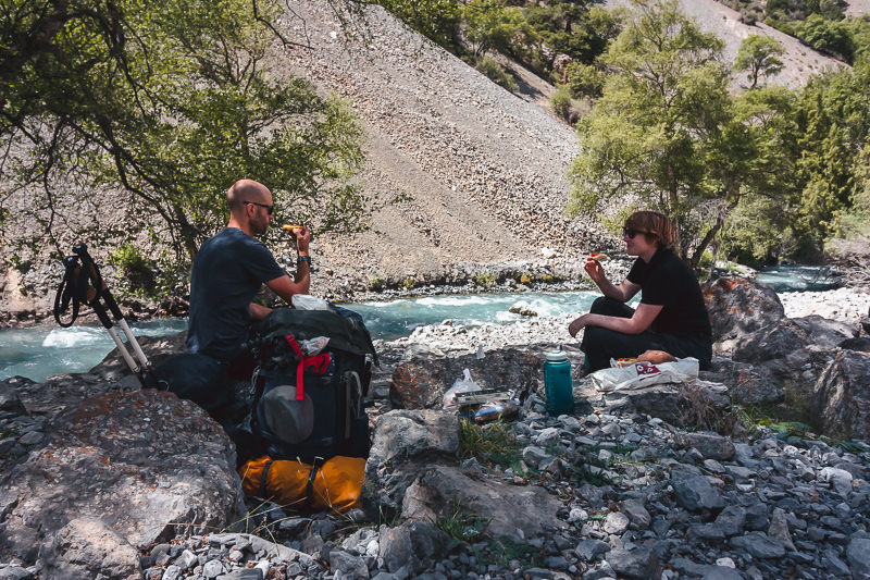 Two hikers eating lunch on shady rocks next to the Sarymat River in Tajikistan's Fann Mountains