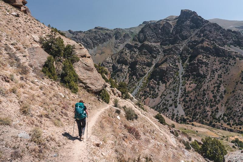 A hiker on a high narrow trail above the Sarymat River in Tajikistan's Fann Mountains