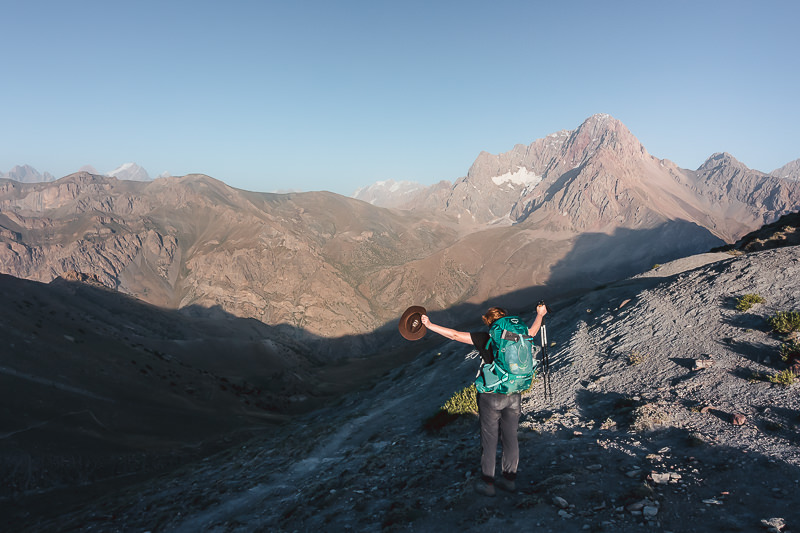 A hiker stands with outstretched arms at Tavasang Pass in the Fann Mountains