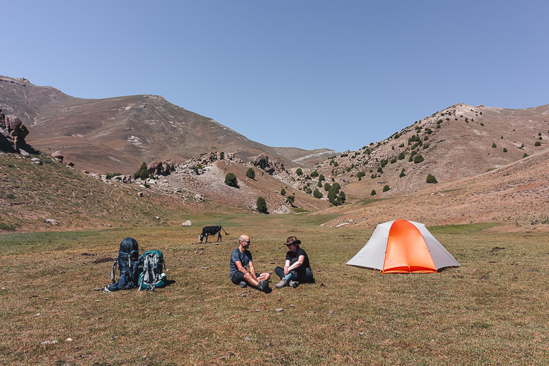 A tent set up next o two hikers in Tavasang Meadow in Tajikistan's Fann Mountains