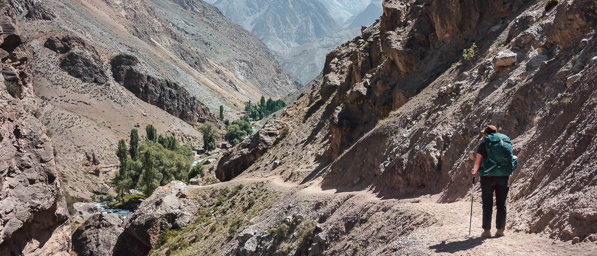 A hiker stares down a narrow path with a steep drop-off to the Sarymat River in Tajikistan's Fann Mountains