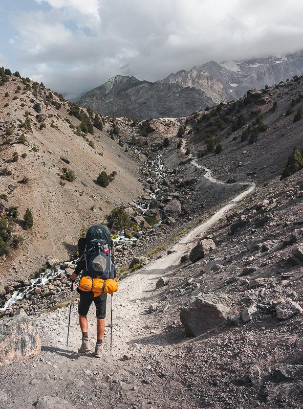 A trekker ascends the long and winding trail to Kulikalon in Tajikistan's Fann Mountains